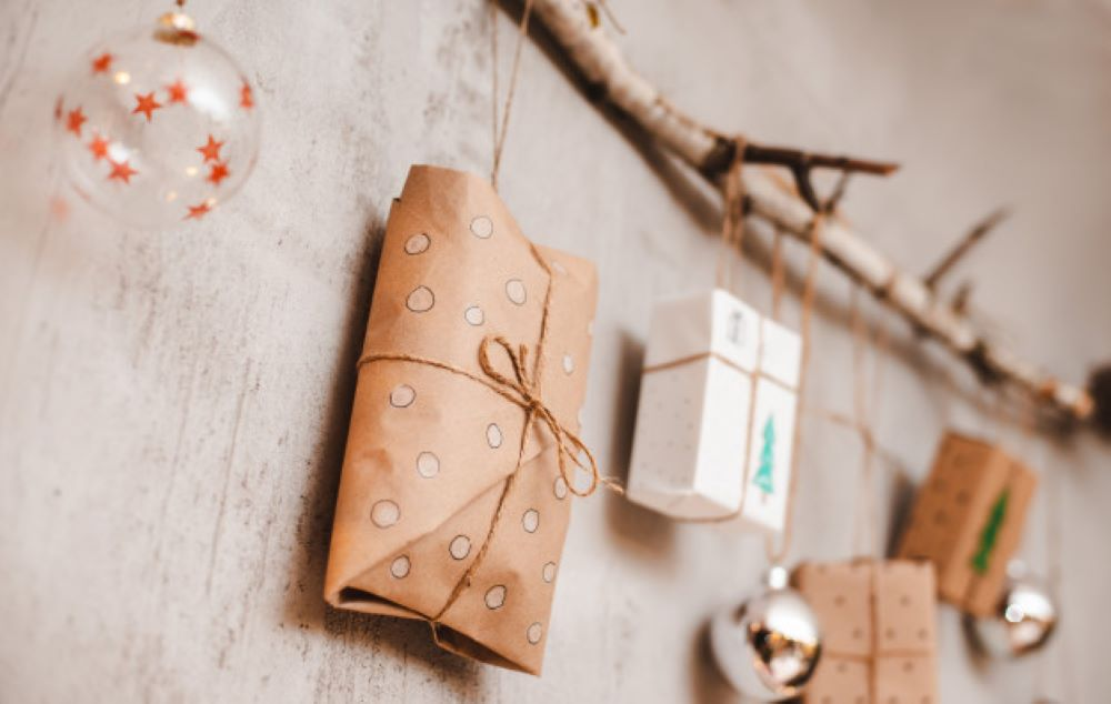 christmas gifts packed with kraft paper hand made decorations hang rope tied stick against gray concrete wall 73683 1374 1