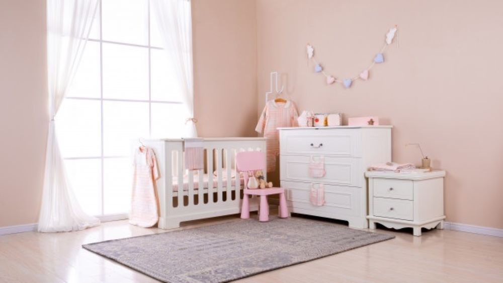 simple white baby bedroom with cot rug